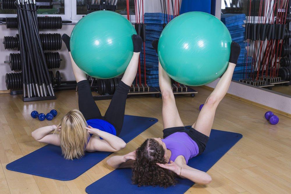 Beine nach oben ziehen mit Gymnastikball zwischen den Beinen